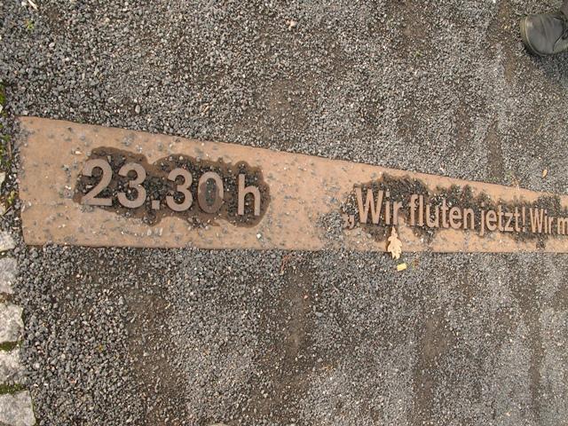 """I gruset på den historiske plads viser denne tidslinje, at Muren blev åbnet kl. 23.30. """"Wir fluten jetzt"""" betyder i fri oversættelse: Vi slipper floden løs. Citat fra en grænsesoldat om den flodbølge af berlinere, der pressede på for at få portene åbnet til Vestberlin."""